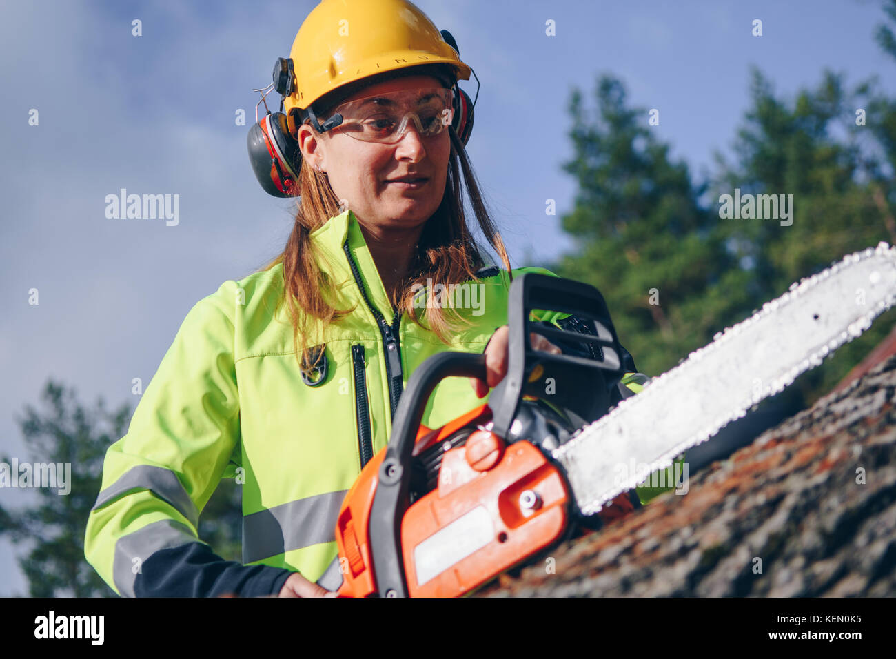 Woman operating chainsaw while wearing safety gear - Stock Image