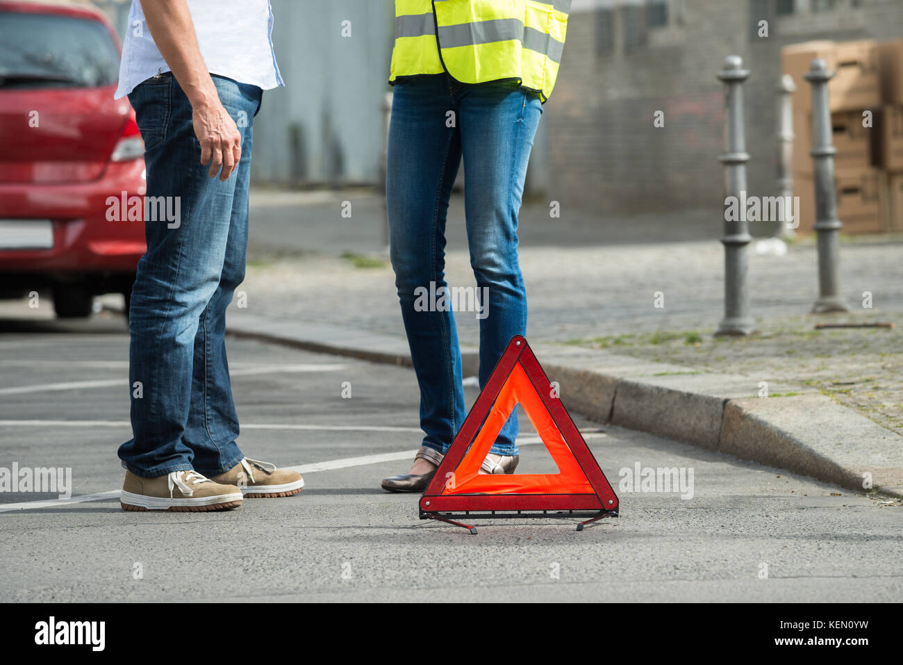 Couple Standing Near Triangular Warning Sign With Broken Down Car - Stock Image