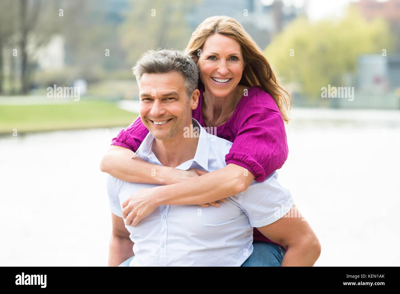 Portrait Of Happy Man Piggybacking His Wife - Stock Image