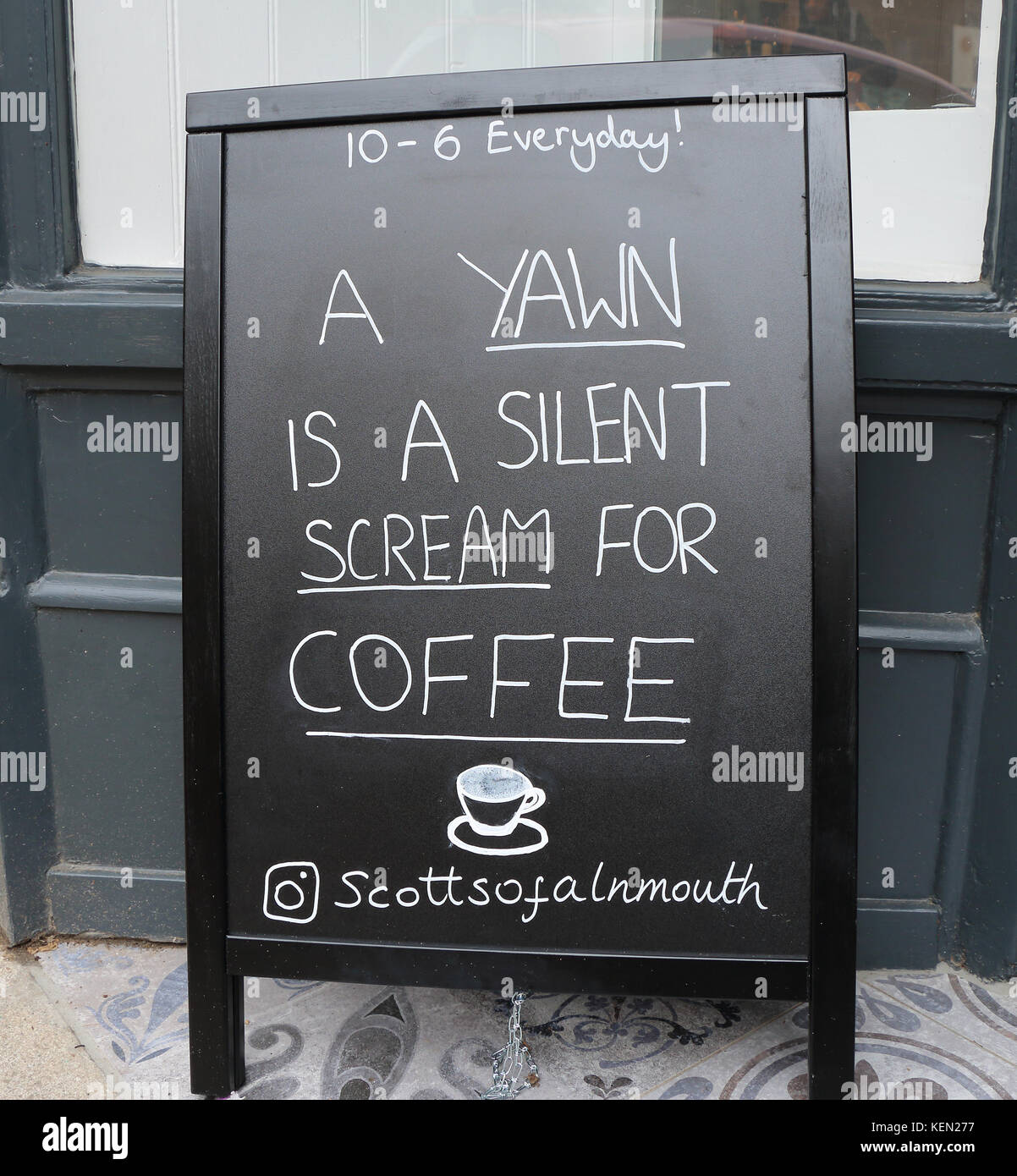 Advertizing board outside a coffee shop in Alnmouth, Northumberland, UK stating A Yawn is a silent scream for coffee - Stock Image