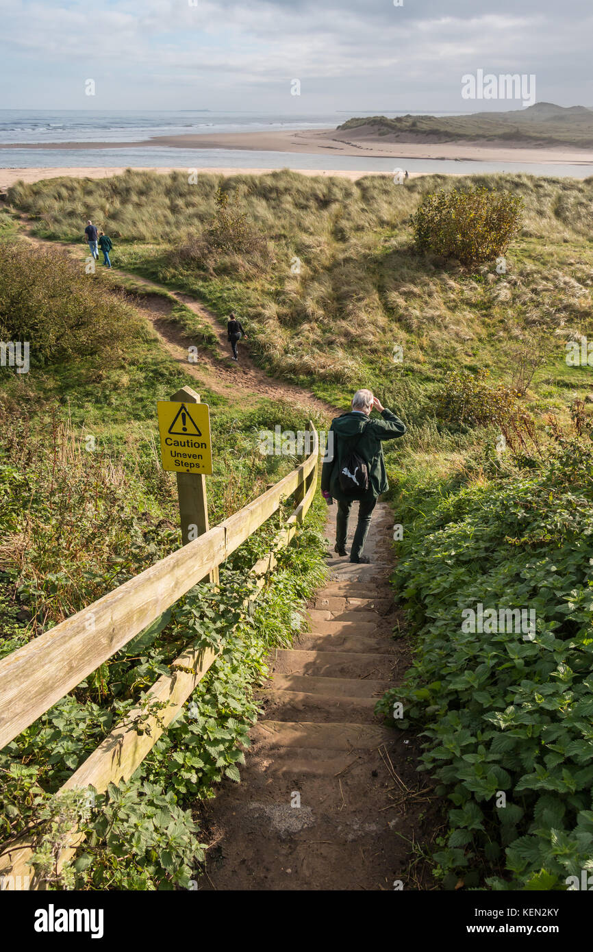 Sign warning of uneven steps and a man walking down them through the dunes at Alnmouth, Northumberland, UK with - Stock Image