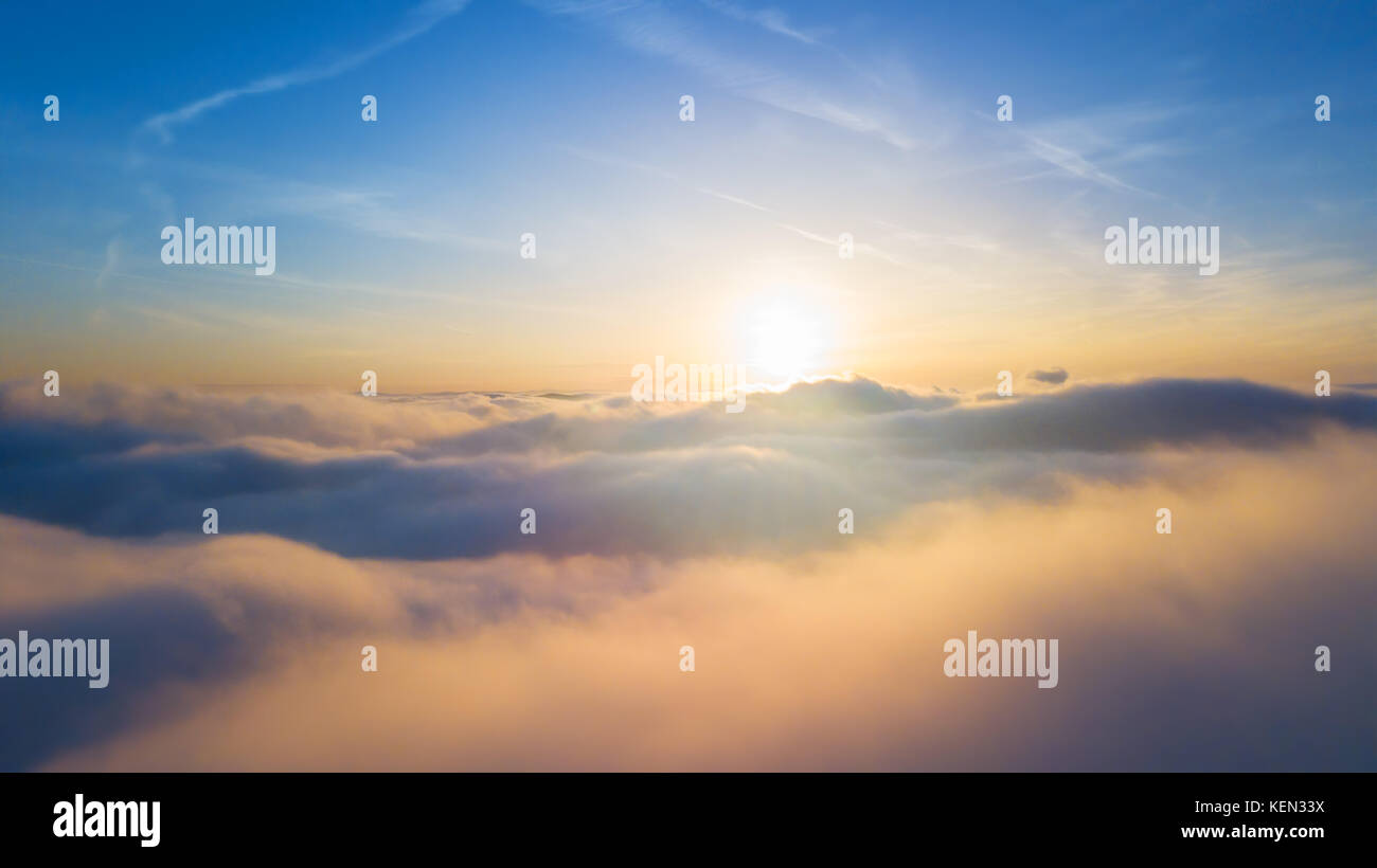 Beautiful sunset above clouds with sunrays - Stock Image