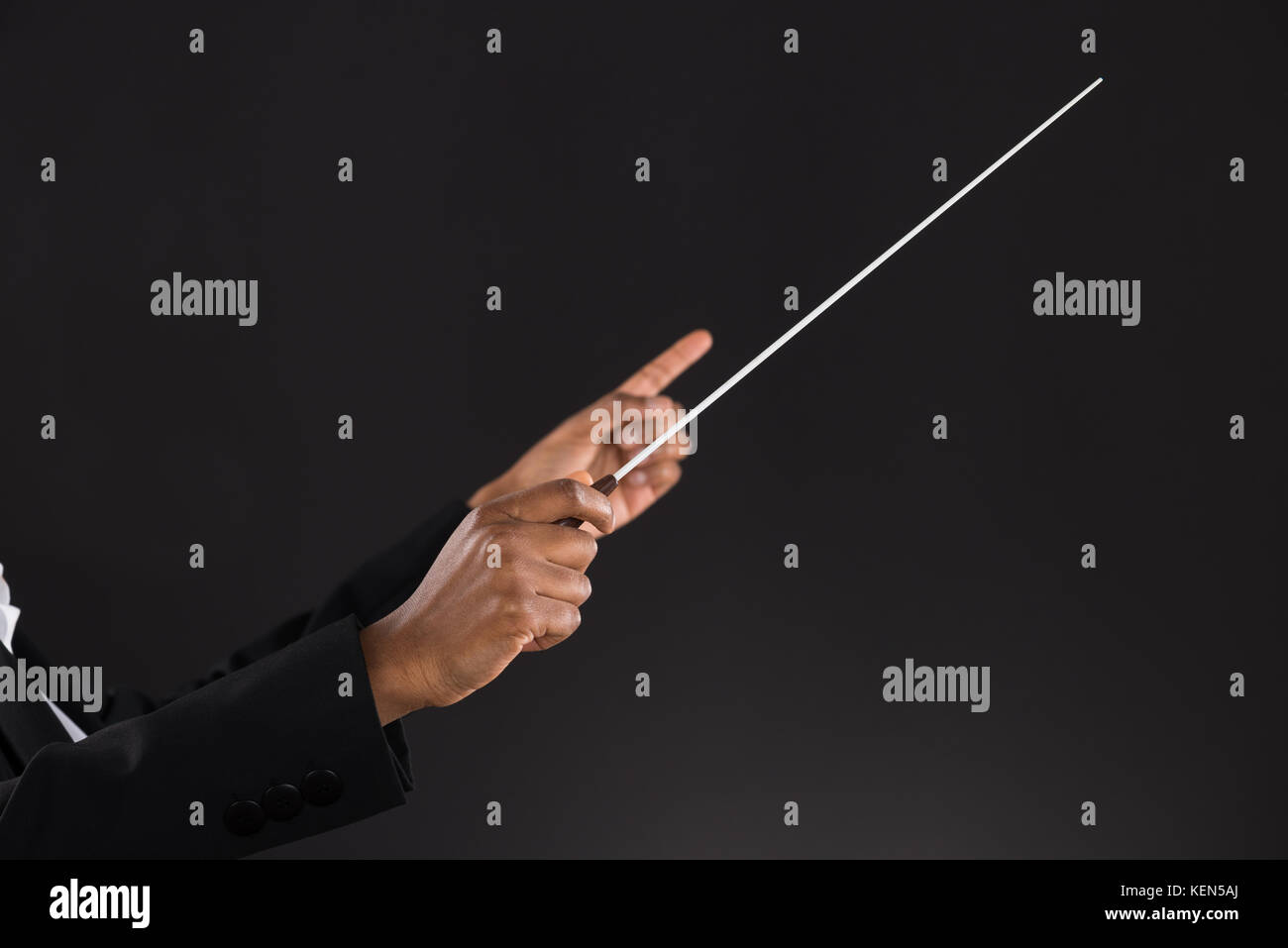 Close-up Of Female Orchestra Conductor Holding Baton Over Black Background - Stock Image