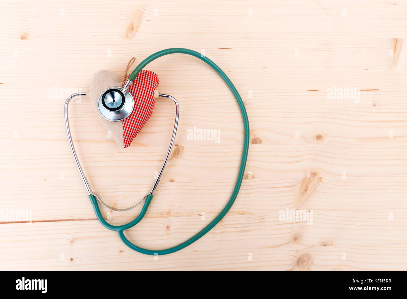 Stethoscope and red fabric heart lying on wooden table. Healthcare, cardiology and medical concept - Stock Image