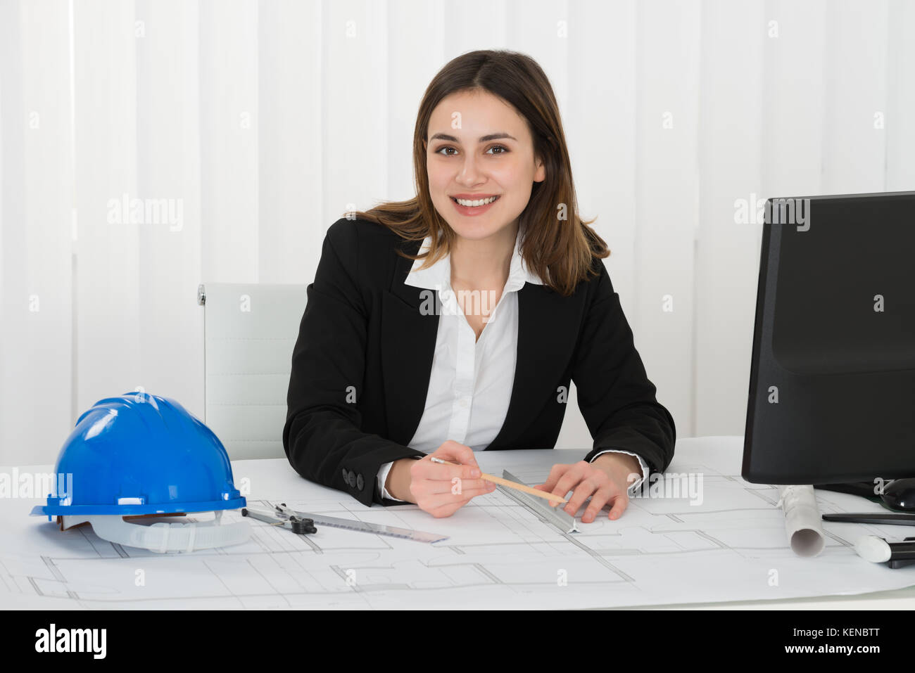 Young Happy Female Architect Drawing Blueprint In The Office - Stock Image
