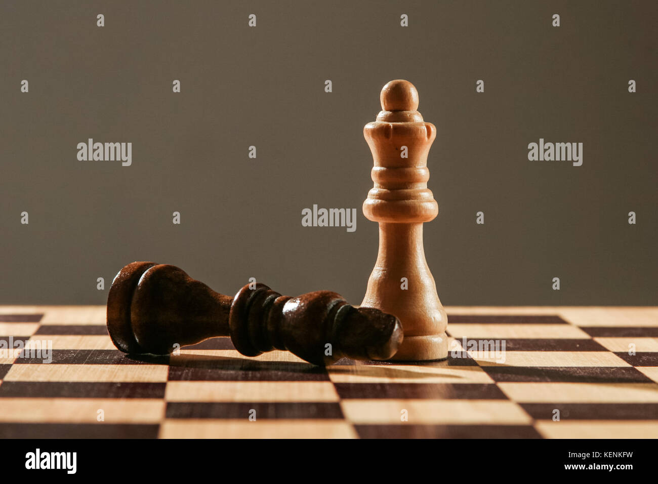 White chess queen, standing over black king, in a wooden chessboard, - Stock Image