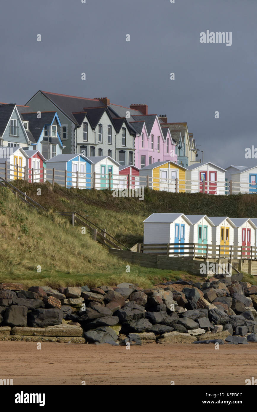 beautiful multi-coloured houses and beach huts above the rocks and sandy beaches at Bude in North Cornwall with - Stock Image