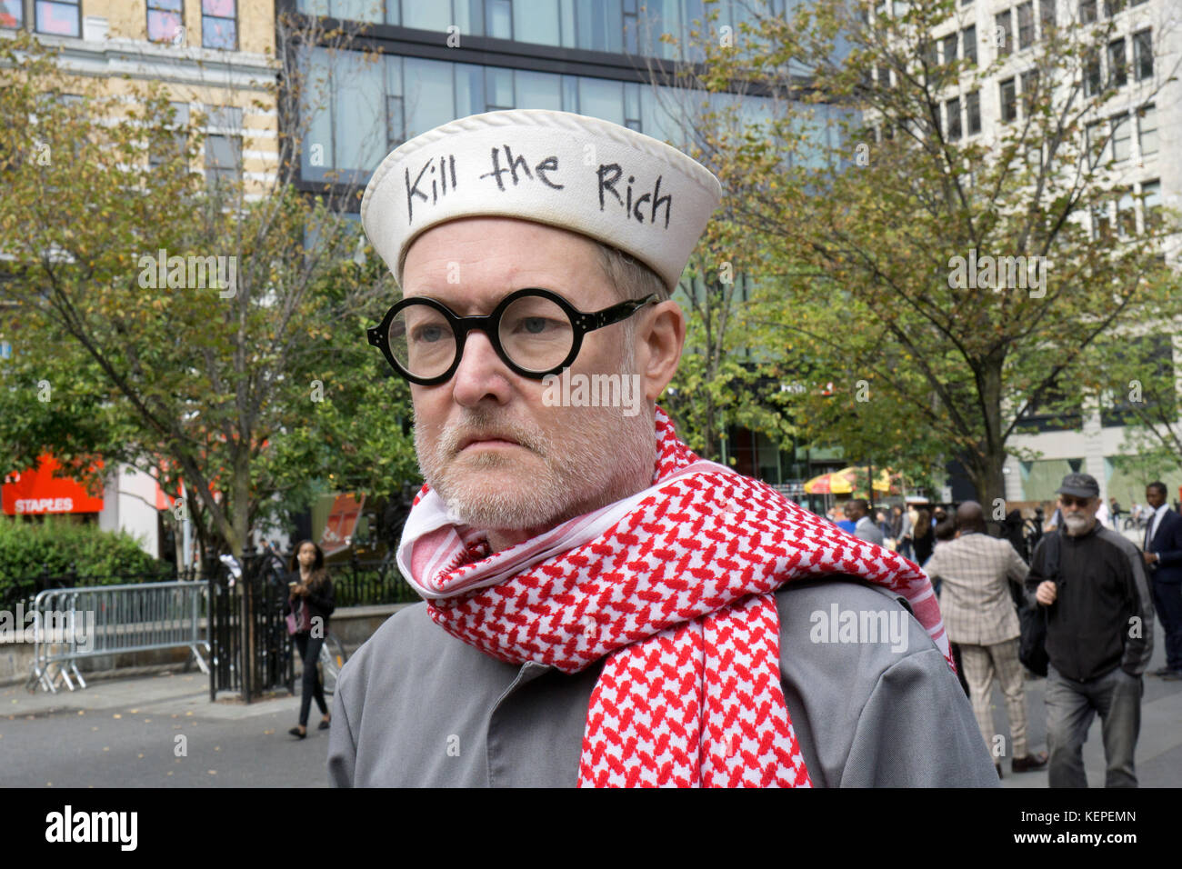 A man wearing a sailor hat that says 'Kill the Rich'in Union Square Park in Manhattan, New York City. - Stock Image