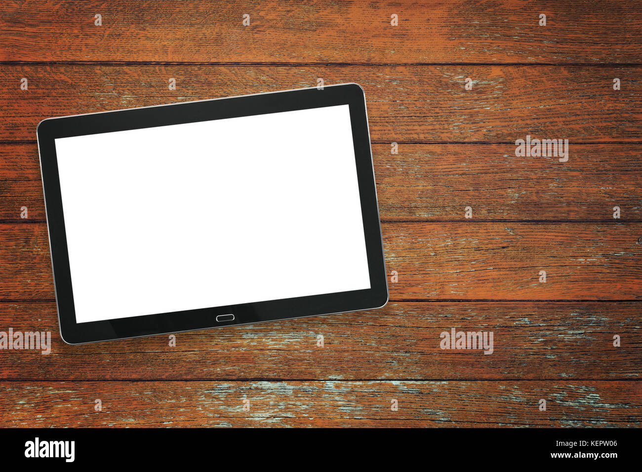 Mockup of a modern black silver digital tablet on a vintage wooden table ( high angel view) - Stock Image