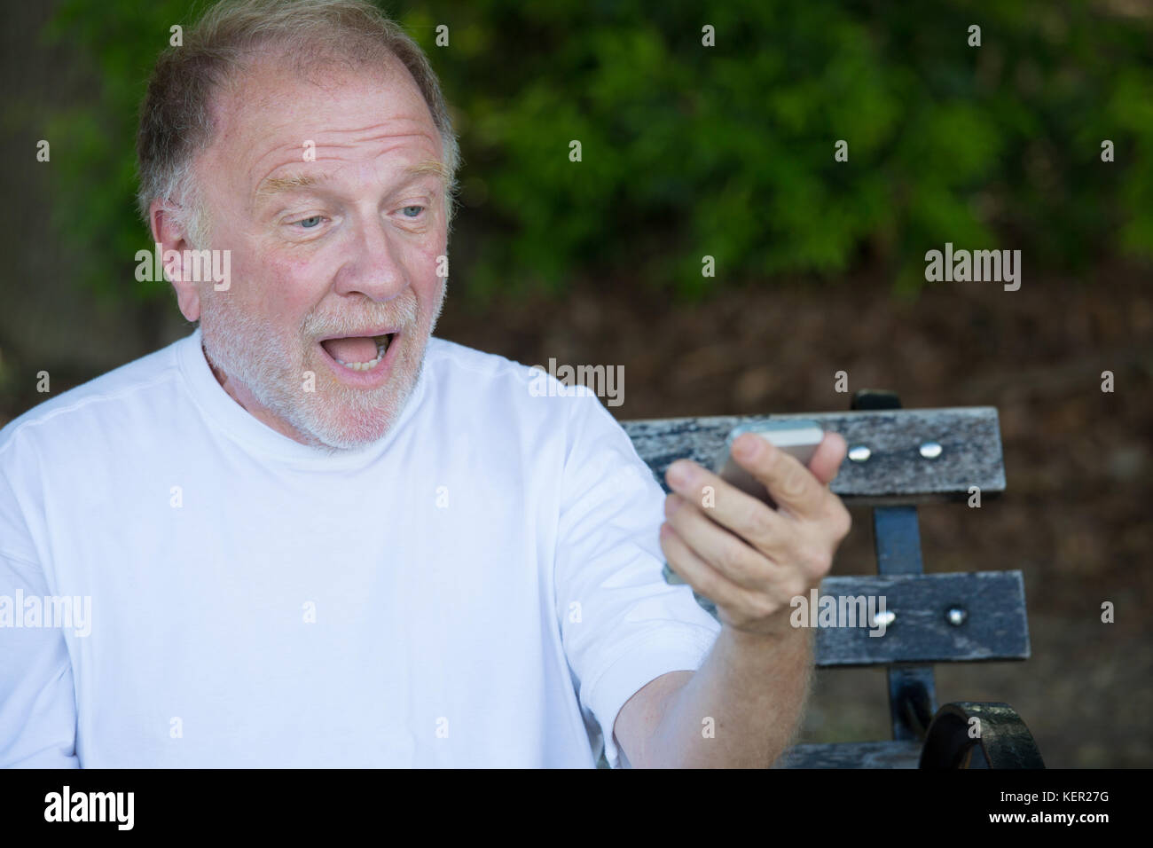 Closeup portrait of bold elderly man in white shirt, shocked at checking smartphone, sending text message, seated - Stock Image