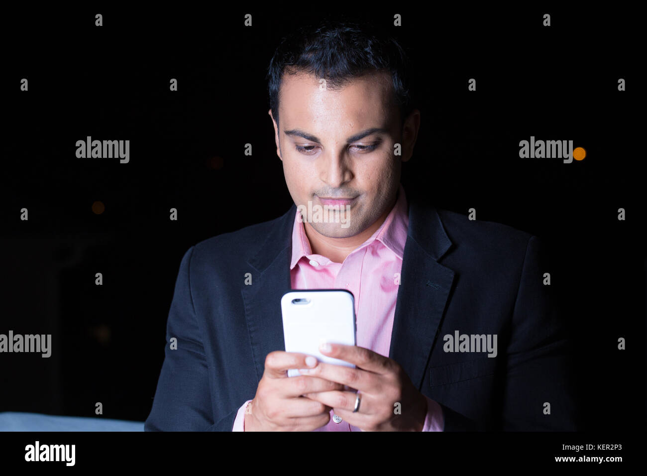 Closeup portrait, young man in black blazer, pink shirt using cell phone, texting at night, isolated outdoors black - Stock Image