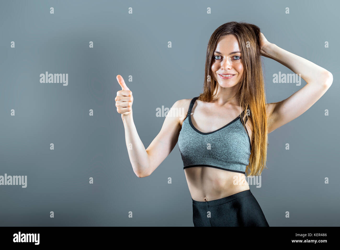 Portrait of Sportswoman with Thumb up Sign - Stock Image