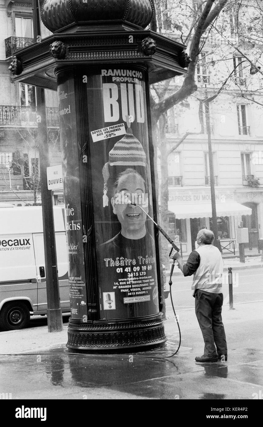 PARIS FRANCE - WORKER WASHING A COLUMN MORRIS - PARIS WORKER -- PILLAR- SHAPED - COLONNE MORRIS -PARIS STREET - - Stock Image