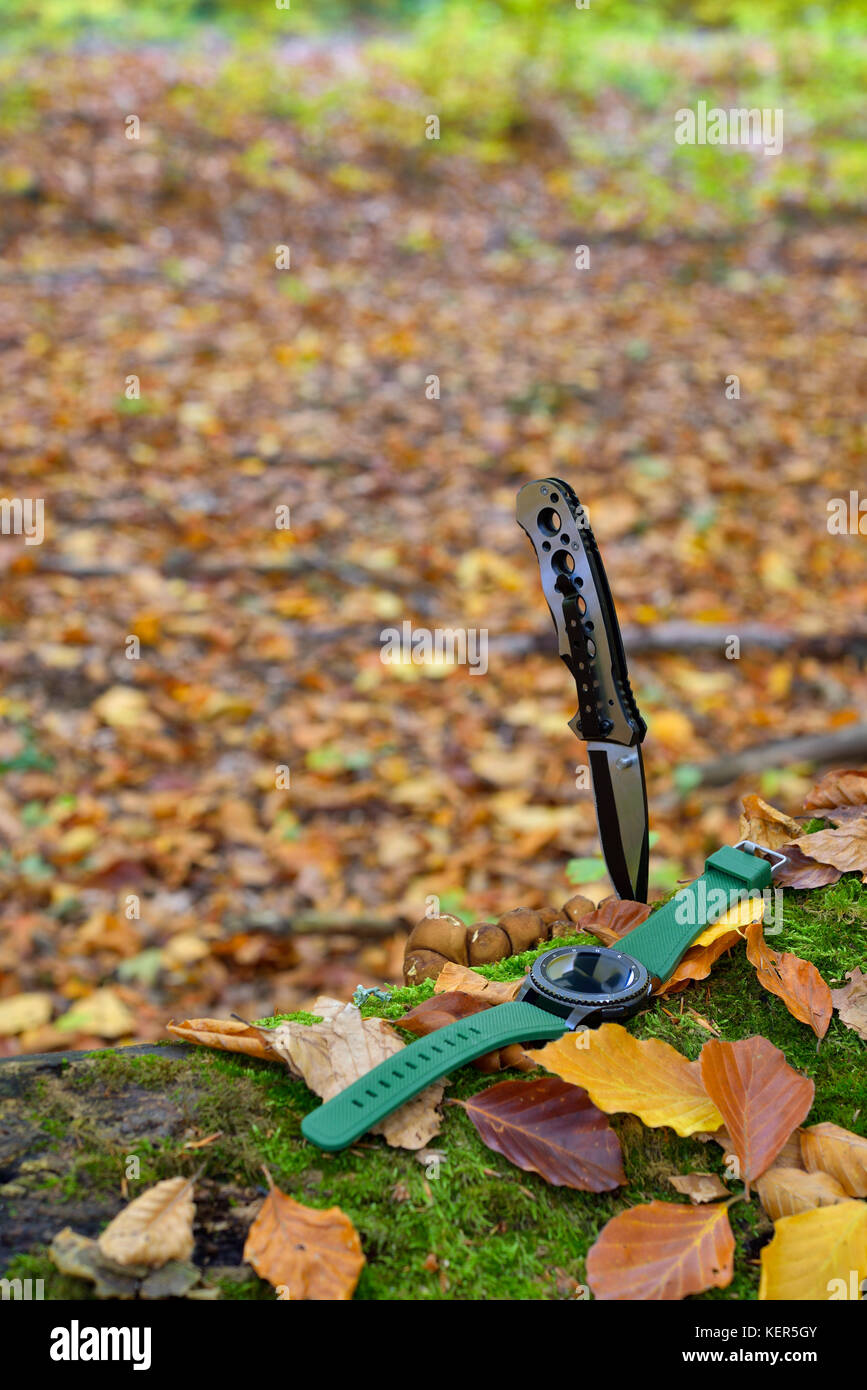 Male set - knives and watches. Black knife and smart watch in autumn forrest - Stock Image