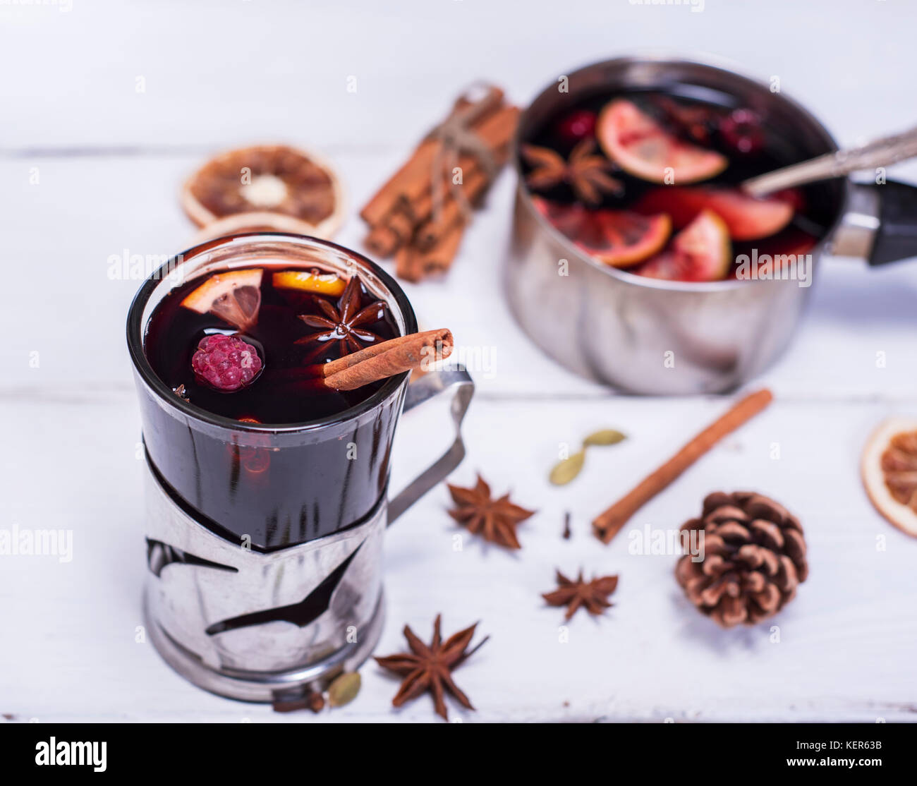 mulled wine in a glass with an iron cup holder on a white wooden background, top view Stock Photo