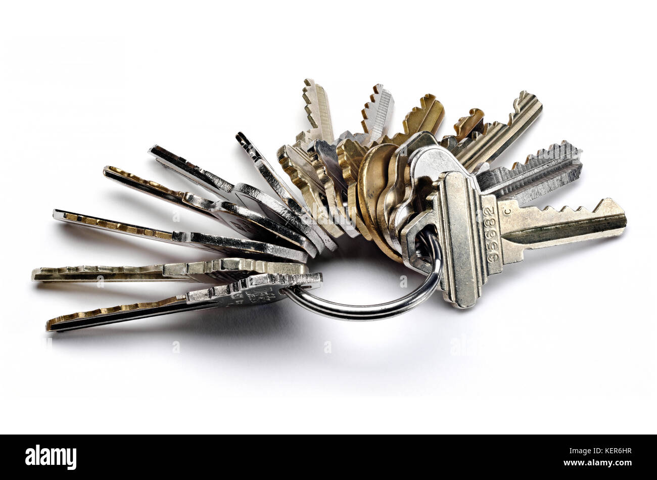 Close up of metal key ring with many worn keys isolated on white - Stock Image