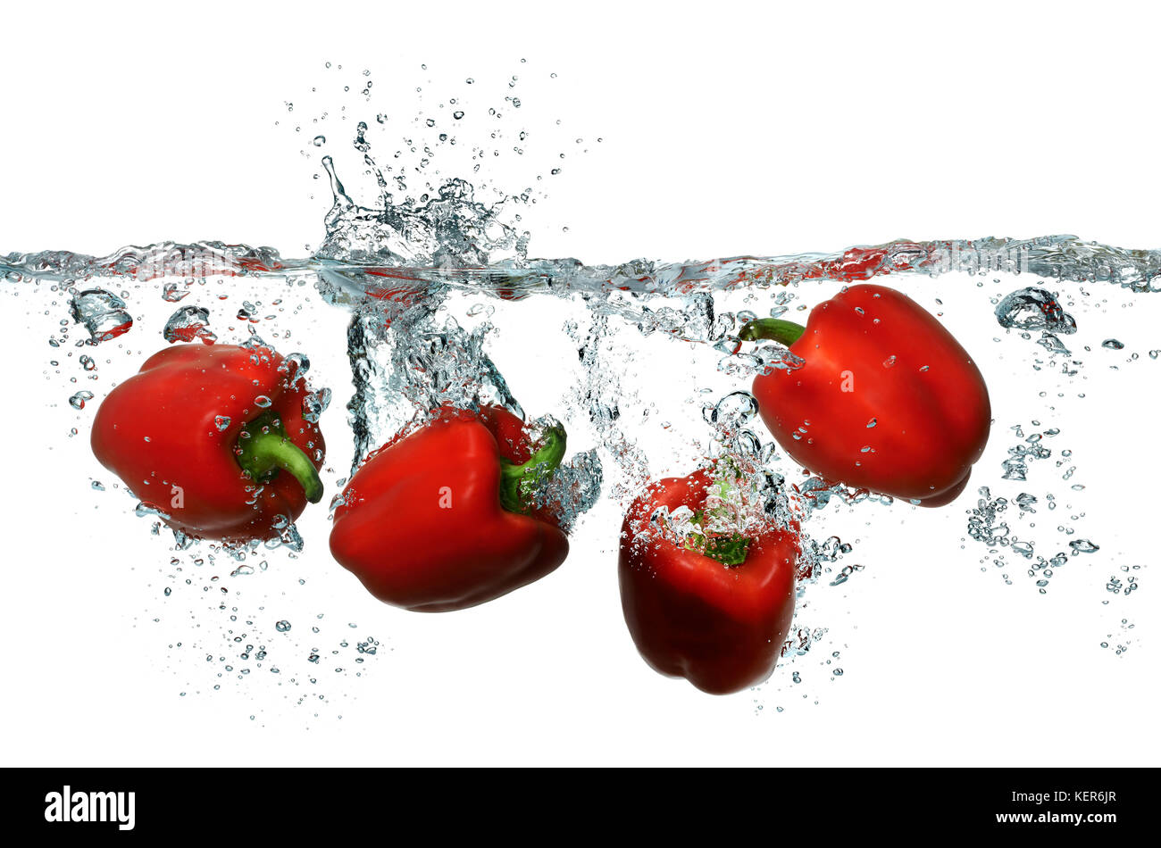 Bright red bell peppers splashing into fresh clean water - Stock Image