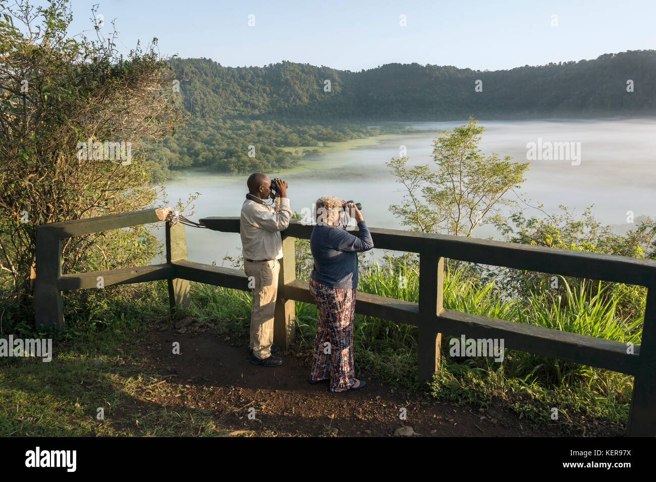 Guide and tourist with binoculars, Ngurdoto Crater, Arusha NP, Tanzania - Stock Image