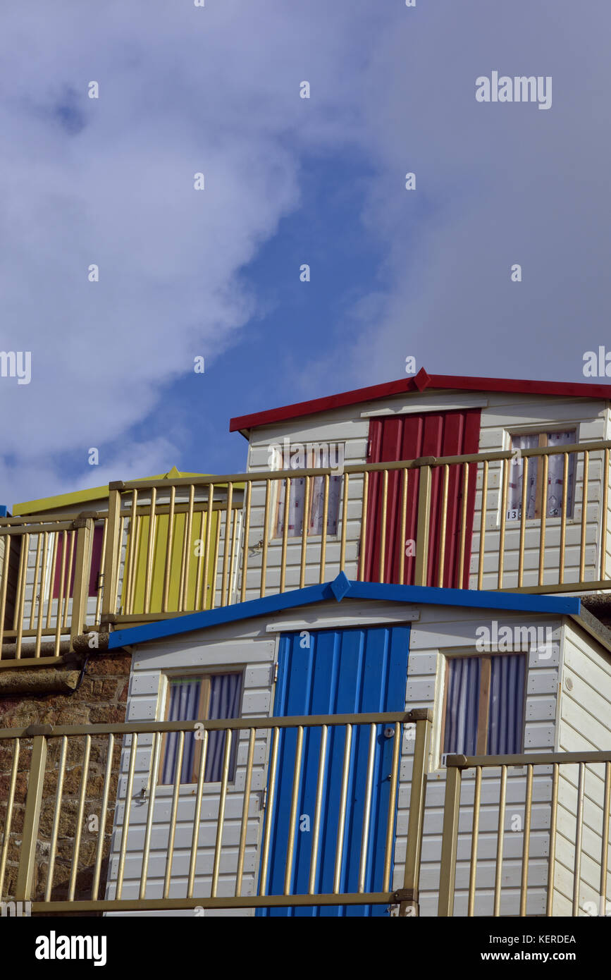 very colourful beach huts at Bude in Cornwall or Devon  against a blue sky with white fluffy clouds in the summer - Stock Image