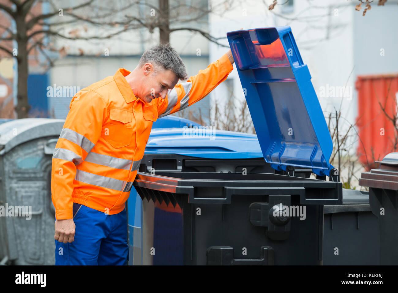 Working Man Looking In Dustbin On Street Stock Photo