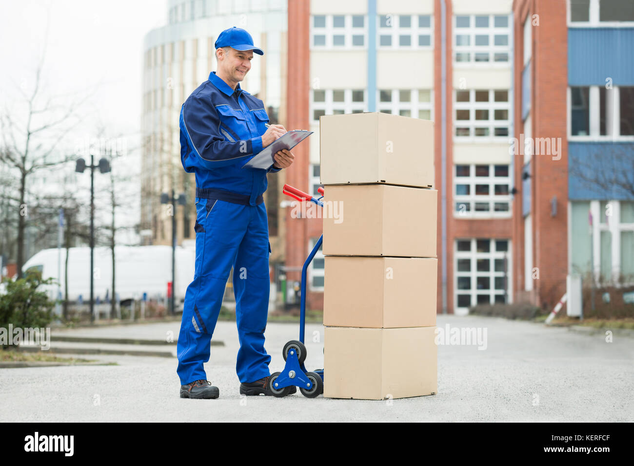 Portrait Of Confident Delivery Man With Parcels And Clipboard Against Truck - Stock Image