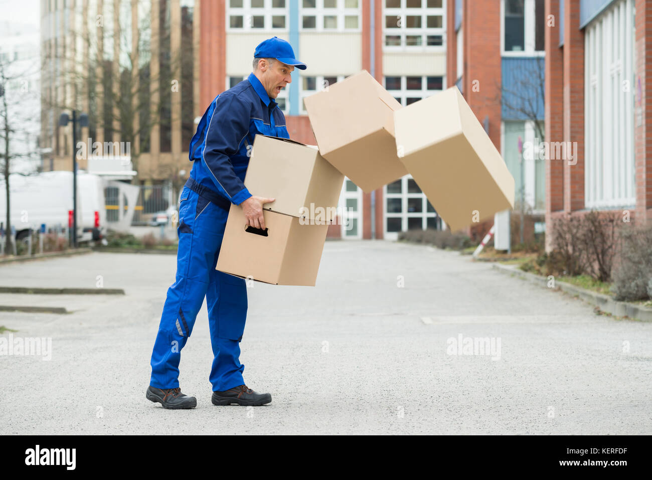 Delivery Man With Falling Stack Of Boxes On Street - Stock Image
