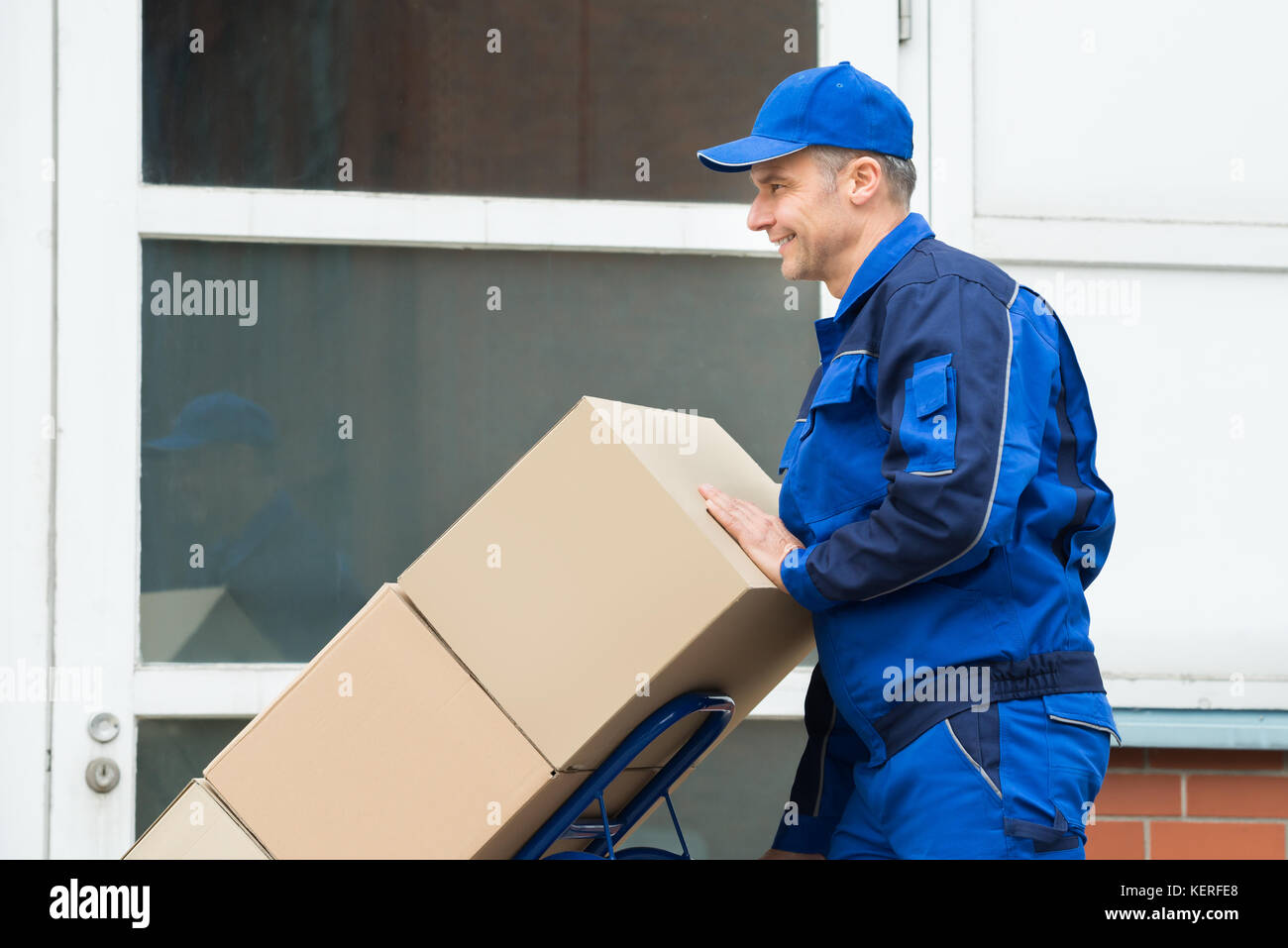 Mature Happy Delivery Man Carrying Boxes On A Hand Truck On Street - Stock Image