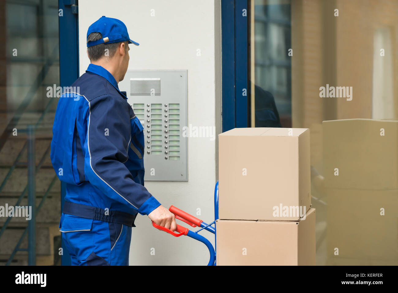 Delivery Man With Trolley Full Of Box Using Security To Enter Building - Stock Image