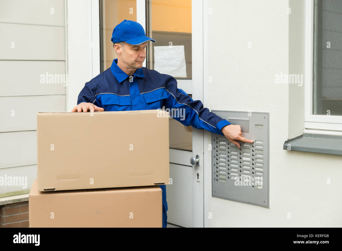 Delivery Man Using Intercom To Enter Home For Delivery - Stock Image