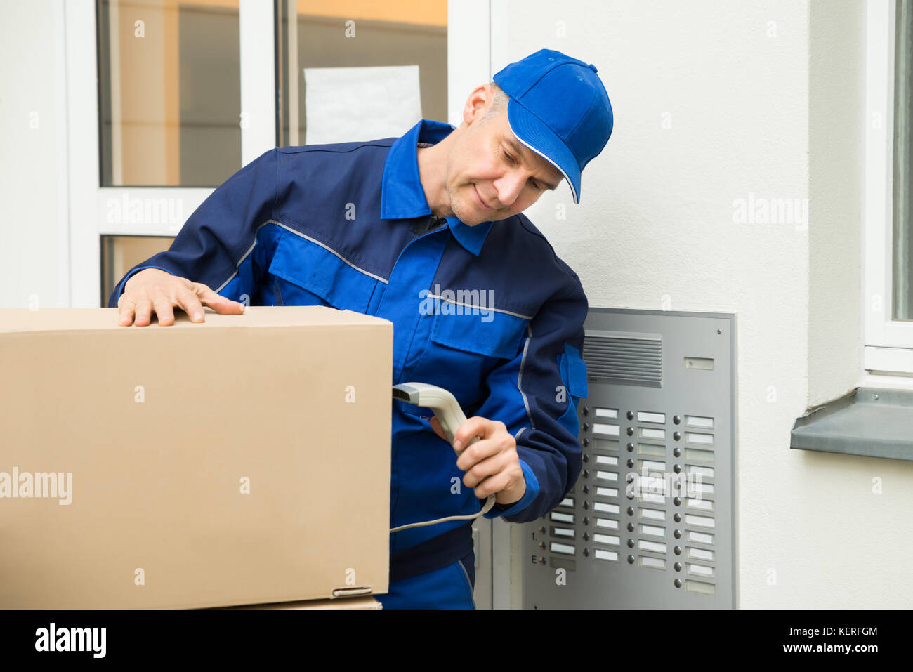 Mature Delivery Man Scanning Cardboard Boxes With Barcode Scanner - Stock Image