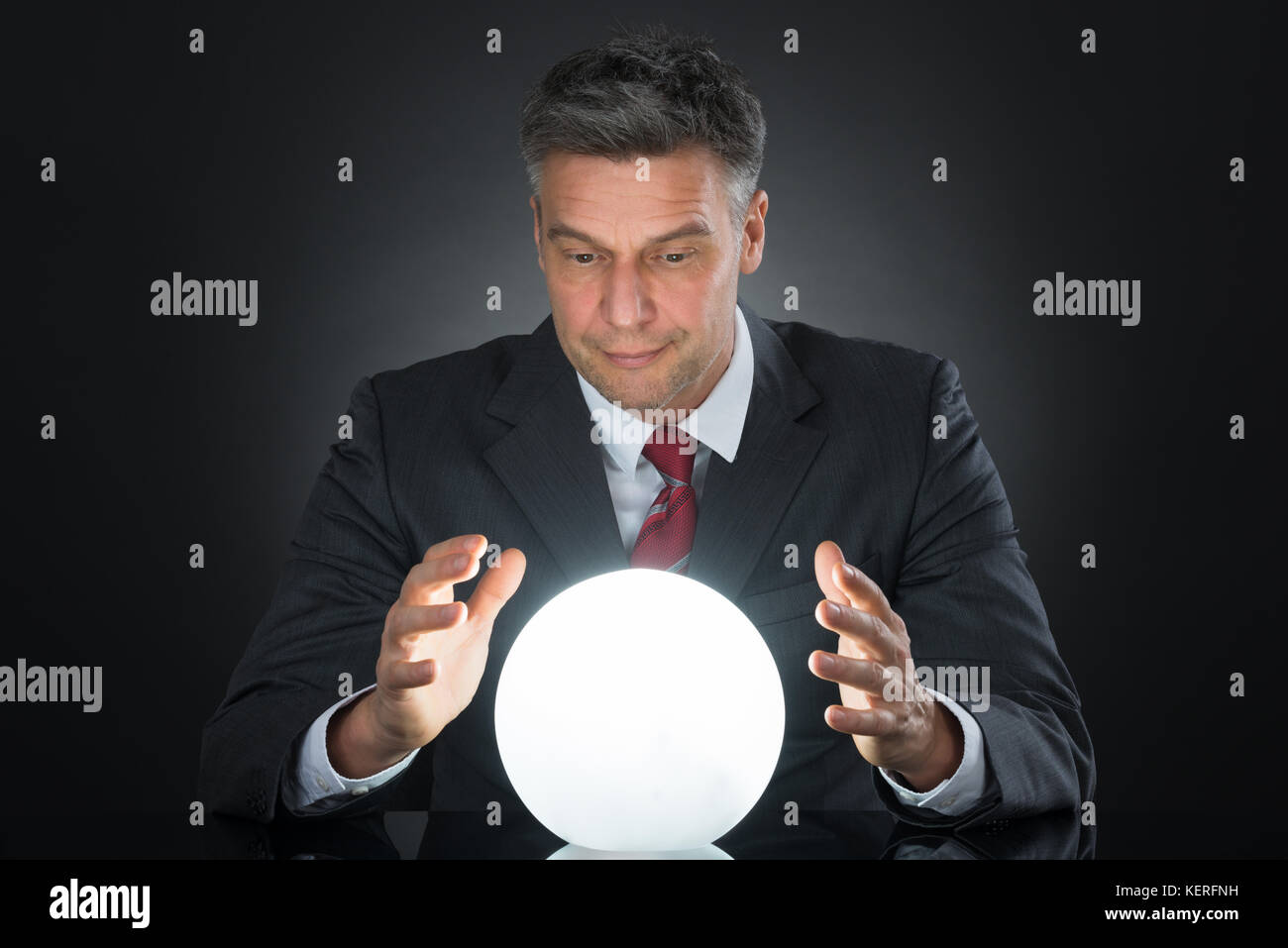 Portrait Of Businessman Predicting Future With Crystal Ball On Desk - Stock Image