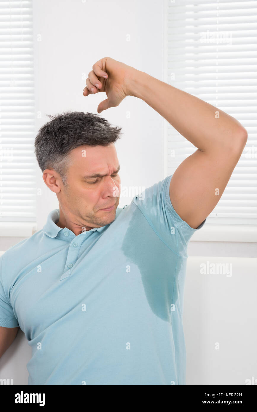 Mature Man Notices His Sweat Under Armpit - Stock Image