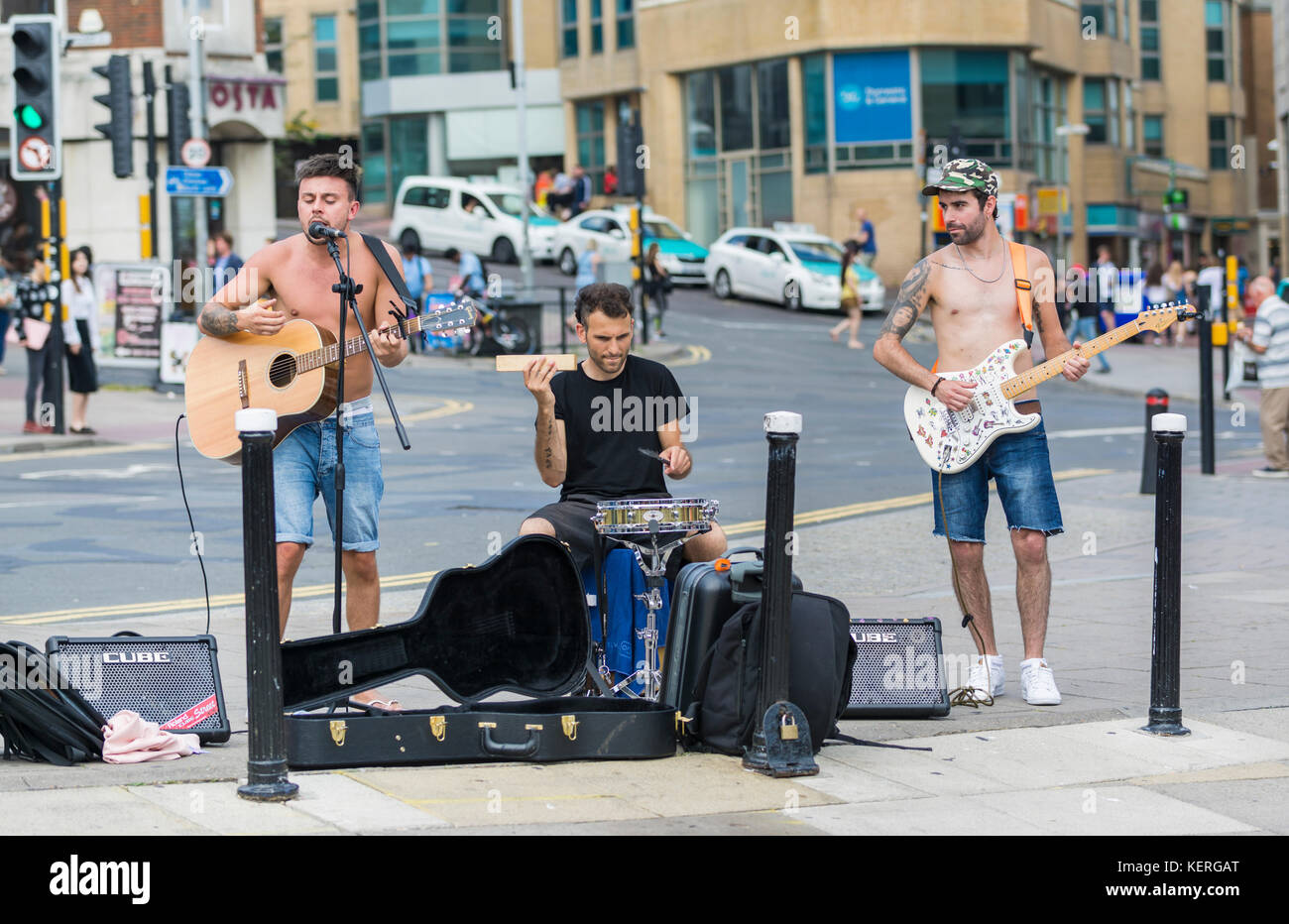 Group of male shirtless buskers singing in the city in Summer in Brighton, East Sussex, England, UK. - Stock Image