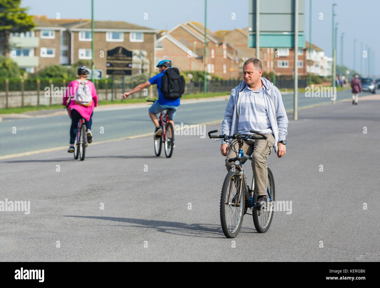 Man cycling without holding onto the handlebars. - Stock Image