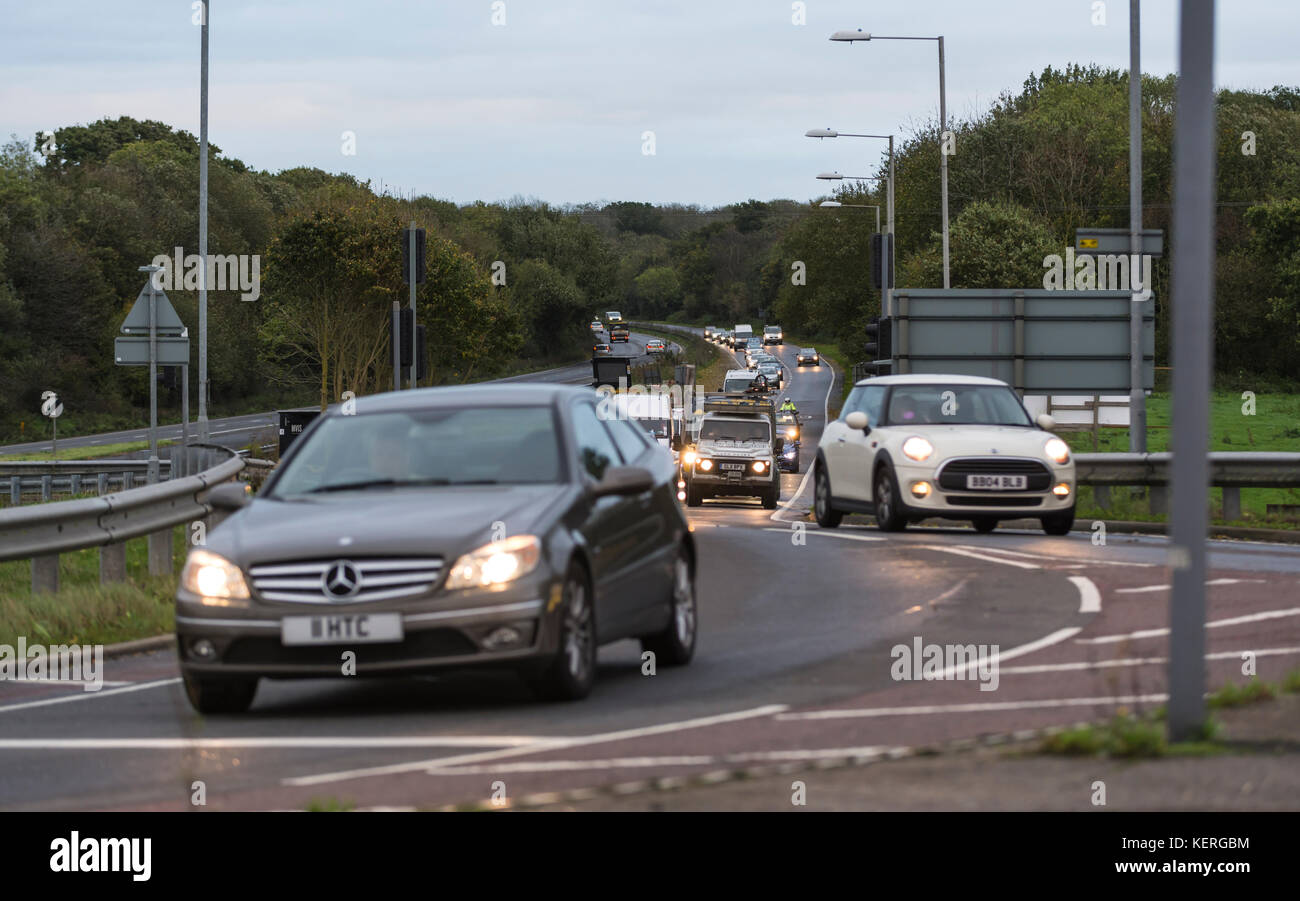Cars with lights on in traffic being driven to work in the early morning rush hour, on the A27 road in the UK. - Stock Image