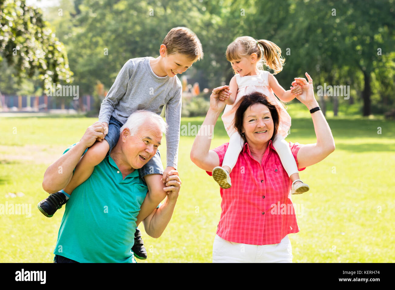 Happy Grandparents Giving Fun Piggyback Ride To Their Grandchildren In Park - Stock Image