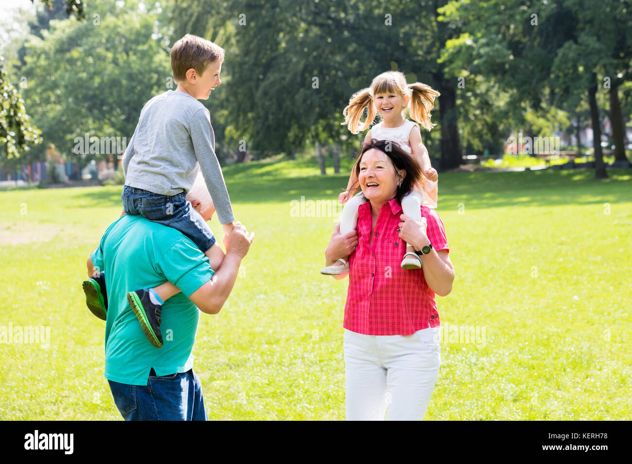 Happy Old Grandparents Giving Piggyback Ride To Their Grandchildren In Park - Stock Image