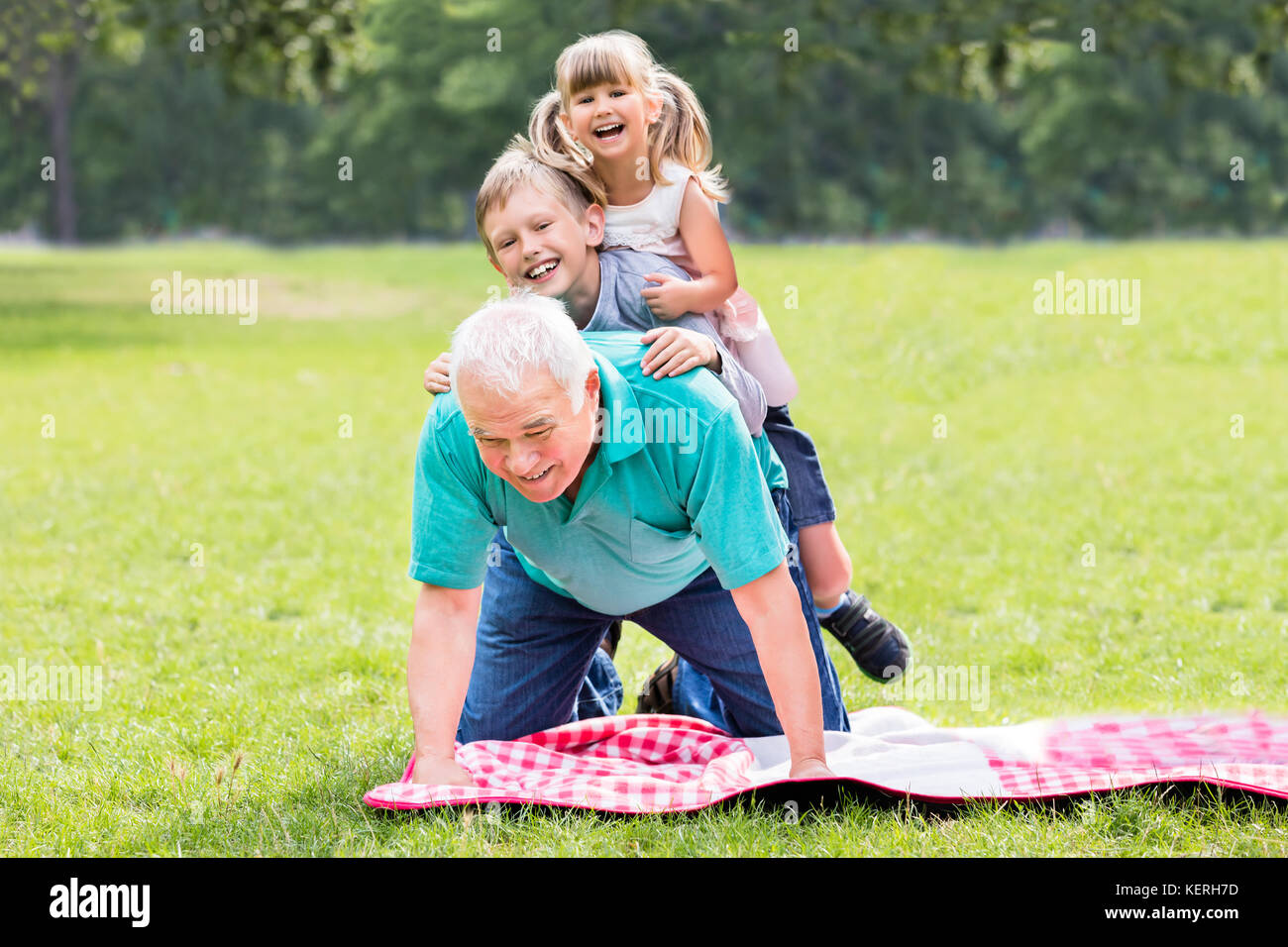 Happy Older Grandfather With Two Kids Lying On Grass In Park - Stock Image