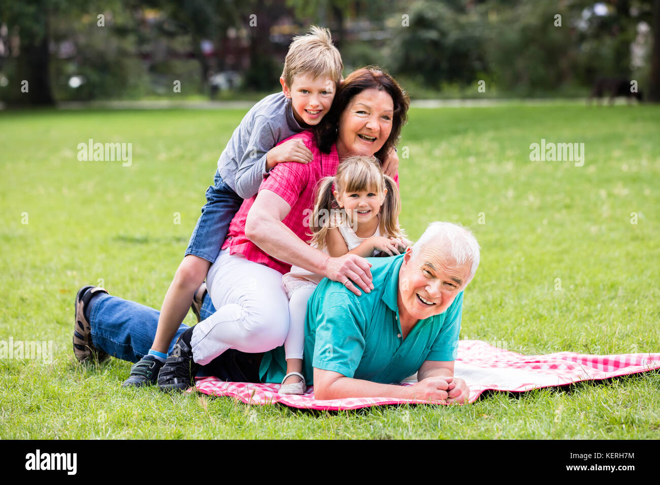 Happy Family Having Fun Lying On Grass In Park - Stock Image