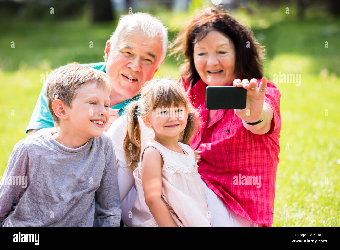 Happy Family Taking Selfie With Phone In Park Stock Photo