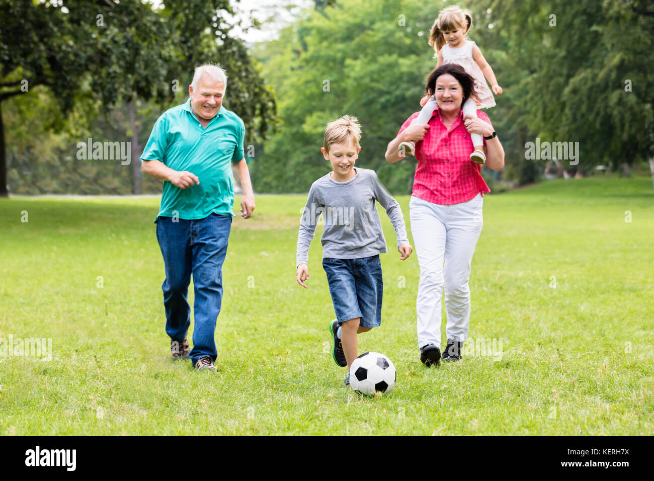 Happy Family Playing Soccer Game Together Running For Ball - Stock Image