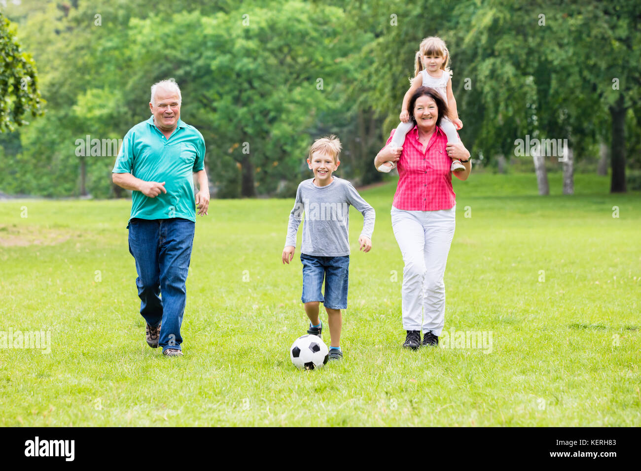 Happy Family Playing Soccer Game With Grandchildren Together In Park. Running For Ball Stock Photo