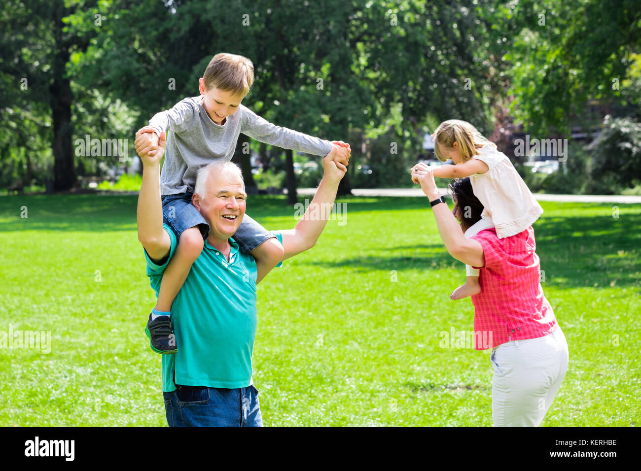 Happy Family Having Fun Doing Piggyback Ride With Kids In Park - Stock Image