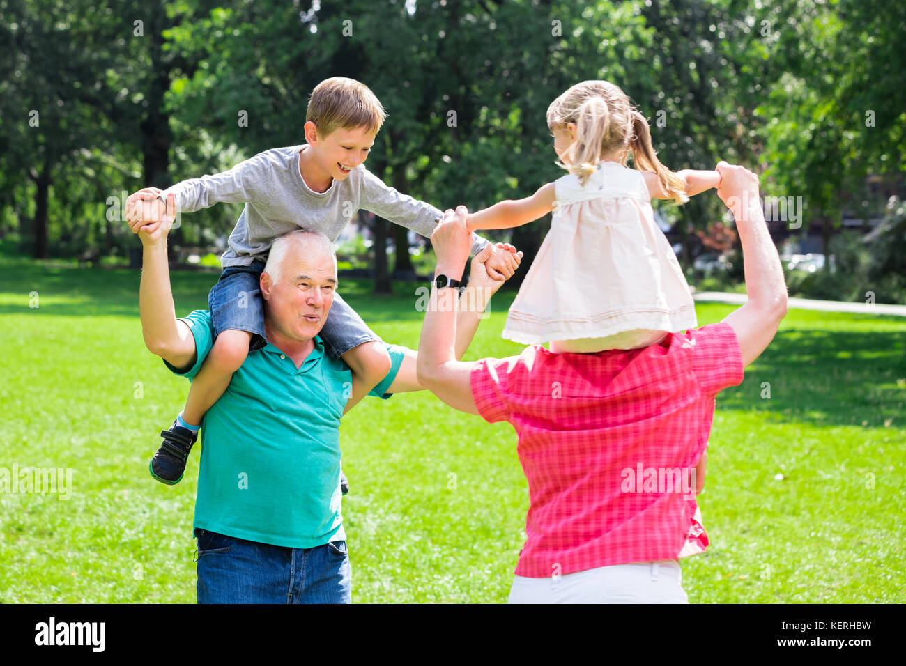 Happy Old Grandparents Enjoy Fun Piggyback Ride With Grandchildren Together In Park - Stock Image