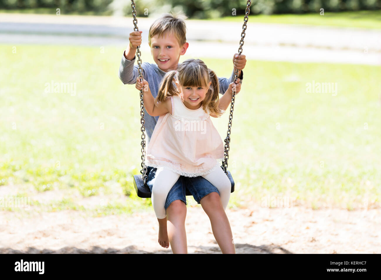 Two Happy Children Enjoying On Swing In The Park Stock Photo