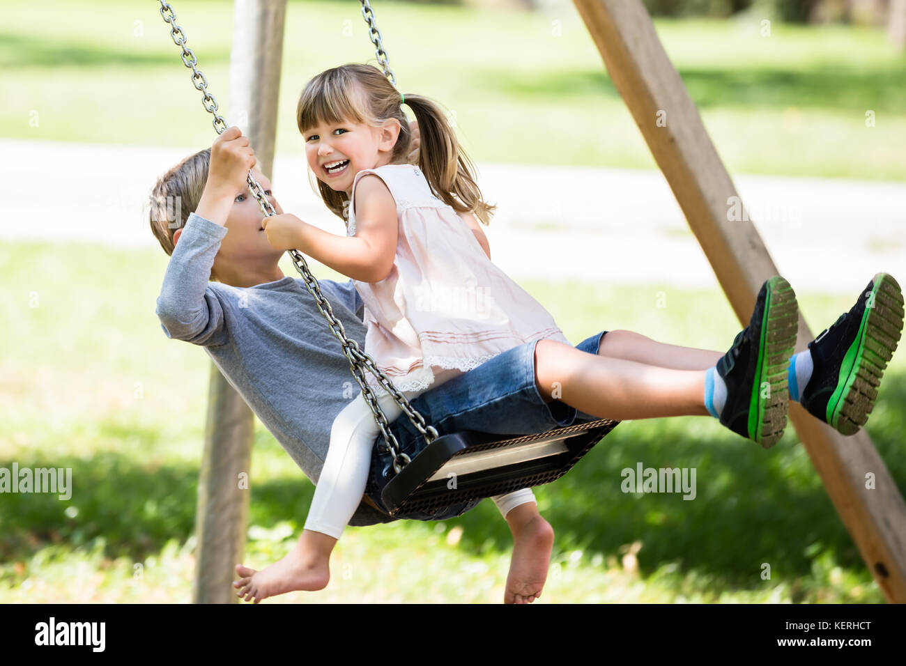 Happy Young Children - Boy and Girl Enjoying On Swing  In The Park - Stock Image
