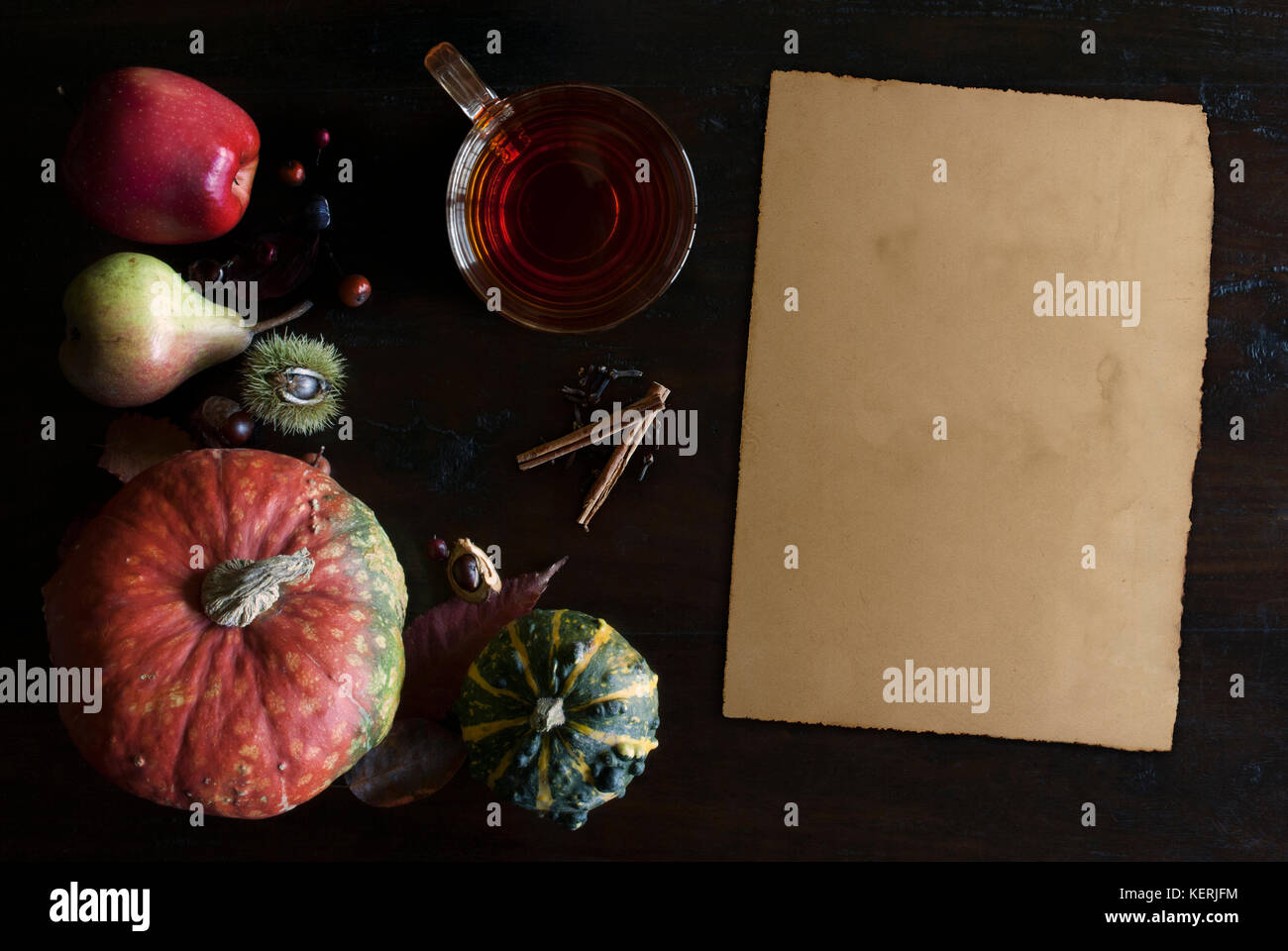 beautiful rustic fall flat lay with glass of tea, leaves, pumpkins, chestnuts and old vintage paper scroll  on wooden - Stock Image