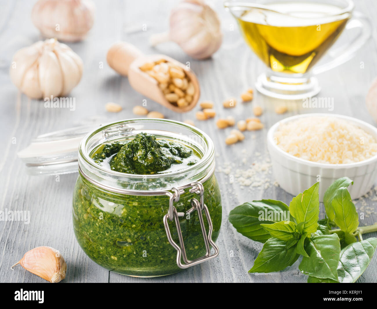 Homemade pesto sauce and ingredients on gray wooden background. Close up wiev of basil pesto in glass jar with ingredients. Stock Photo