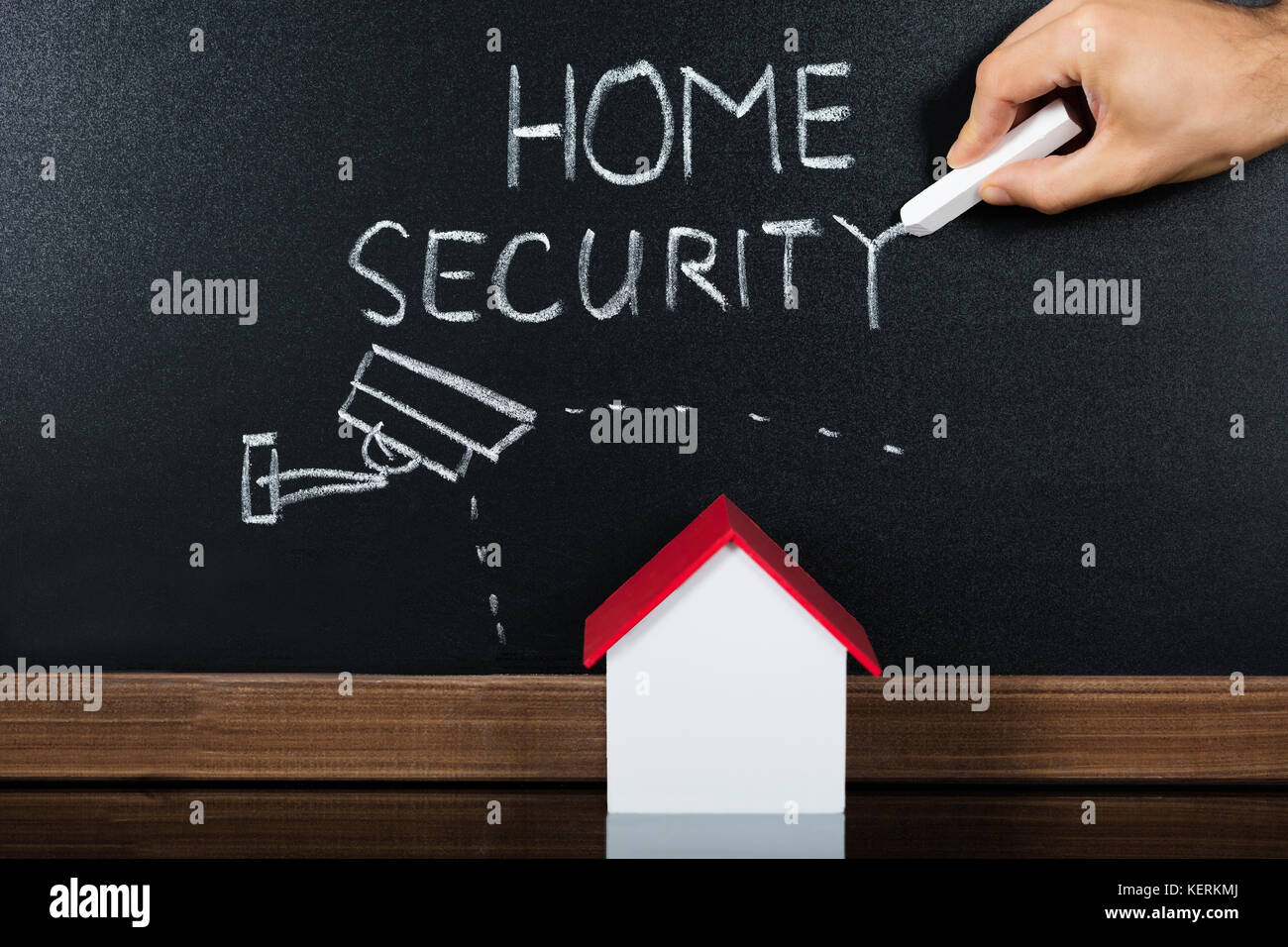 Person Hand Showing Home Security Concept On Blackboard In Front Of House Model - Stock Image