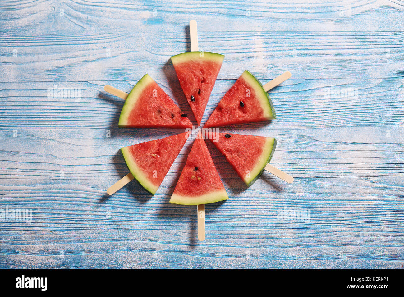 Slices of juicy red watermelon on a wooden background - Stock Image
